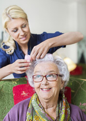 Female caretaker putting curlers to senior woman's hair at nursing home - MASF05065