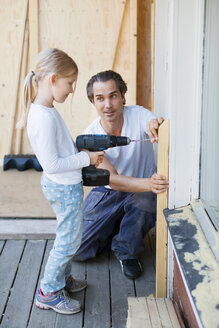 Father assisting girl in using cordless screwdriver while home improving - MASF05074