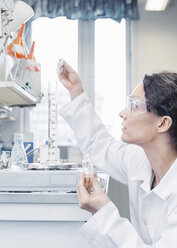 Female scientist pouring chemical in beaker at laboratory - MASF05086