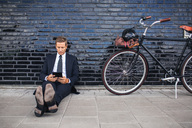 Full length of businessman using digital tablet while sitting on sidewalk by bicycle - MASF05101