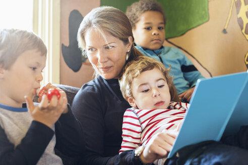 Female teacher telling story to children in kindergarten - MASF05107