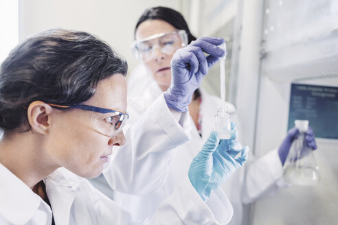 Female scientists examining chemical in laboratory - MASF05116