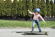 Full length of boy balancing on skateboard at yard - MASF05122