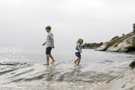 Greece, Chalkidiki, brother and little sister playing together on the beach - KMKF00158