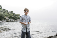 Greece, Chalkidiki, portrait of blond boy standing in front of the sea holding stone - KMKF00164