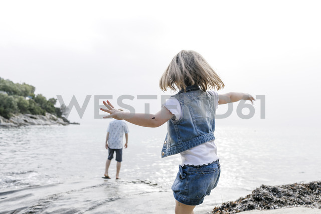 Greece, Chalkidiki, back view of little girl playing on the beach - KMKF00167