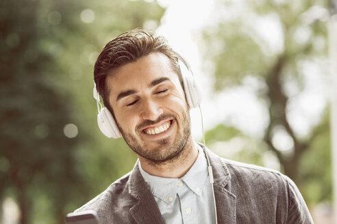Businessman enjoying music through headphones outdoors - MASF05134