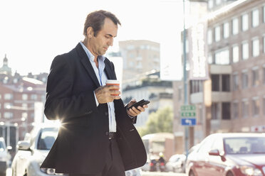 Businessman using mobile phone and holding disposable coffee cup while walking on city street - MASF05146