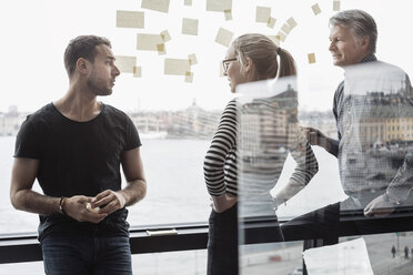 Business colleagues discussing by glass window in office - MASF05170