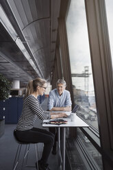 Business people sitting at table by window in office - MASF05173