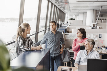 Business people discussing at cubicle in office - MASF05176