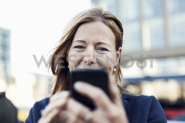 Businesswoman using mobile phone outdoors - MASF05203