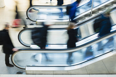 Side view blurred motion of people using escalator in mall - MASF05236