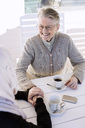 Young female home caregiver consoling senior woman while having coffee on porch - MASF05317