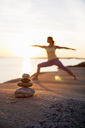 Woman practicing yoga warrior pose on lakeshore with focus on stack of stones - MASF05347