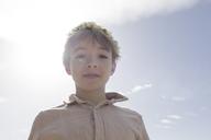 Portrait of boy wearing flowers at backlight - KMKF00181