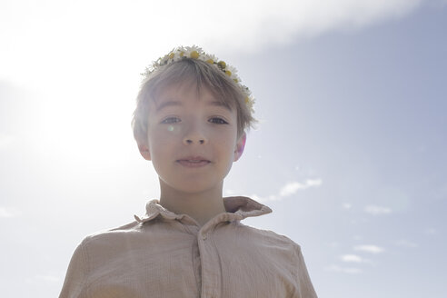 Portrait of boy wearing flowers at backlight - KMKF00181