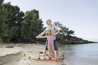 Brother and little sister playing together on the beach - KMKF00184