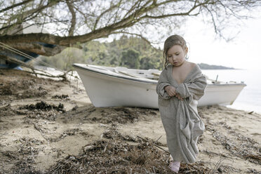 Sad little girl wrapped in oversized cardigan standing on the beach - KMKF00187