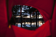 View of trees and lake through camping tent at dusk - MASF05357