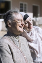 Smiling senior woman and female home caregiver in front of house - MASF05360