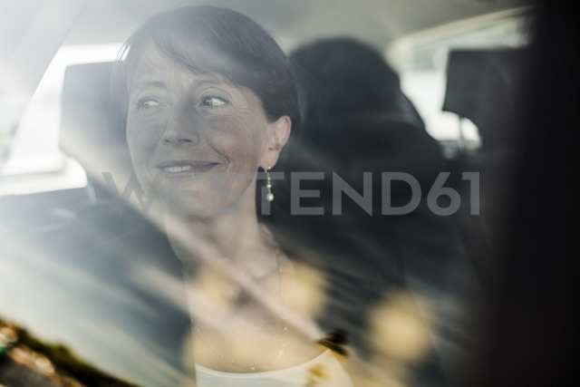 View of businesswoman smiling while looking out through taxi window - MASF05366