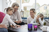 Three generation females playing card puzzle game at home - MASF05384