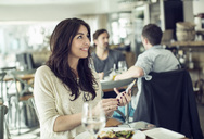 Smiling businesswoman holding mobile phone in restaurant - MASF05420