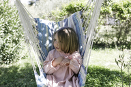 Little girl sitting on hammock in the garden - KMKF00190