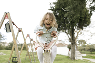 Excited little girl having fun on a seesaw - KMKF00202