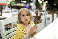 Greece, portrait of little girl sitting in a restaurant with two Souvlaki meat skewers - KMKF00205