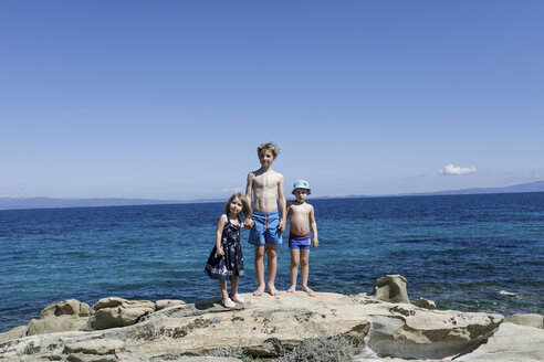 Greece, Chalkidiki, three children stamnding hand in hand on rock in front of the sea - KMKF00208