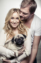Portrait of happy pregnant woman holding pug dog with man embracing her from behind - MASF05422