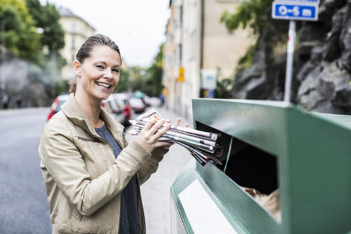 Portrait of smiling woman putting newspapers in recycling bin - MASF05443