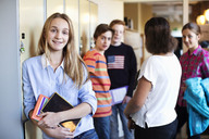 Portrait of school girl standing at locker room with friends in background - MASF05455
