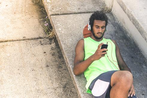 Basketball player listening music, smartphone and headphones - FMOF00334