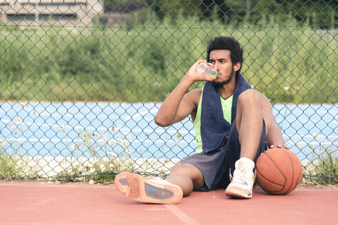 Young basketball player drinking from water bottle - FMOF00355