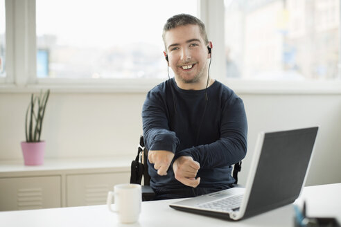 Portrait of happy disabled businessman with laptop at desk in office - MASF05497