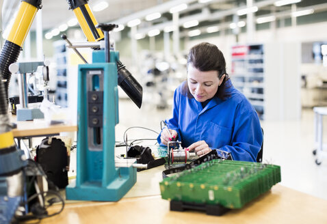 Mid adult female electrician working on circuit board at desk in industry - MASF05518