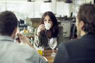 Mature woman drinking coffee while looking at colleague during lunch meeting in restaurant - MASF05542