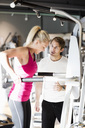 Instructor motivating customer exercising at gym - MASF05563