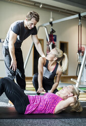 Instructors with senior woman doing sit-ups at health club - MASF05566