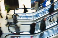 High angle view of people using escalator in shopping mall - MASF05575