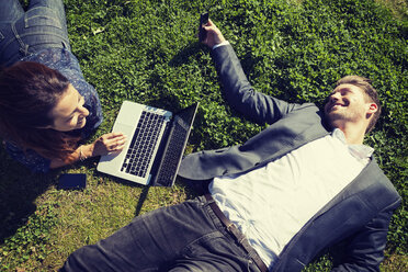 High angle view of business people with laptop lying on grass at park - MASF05584