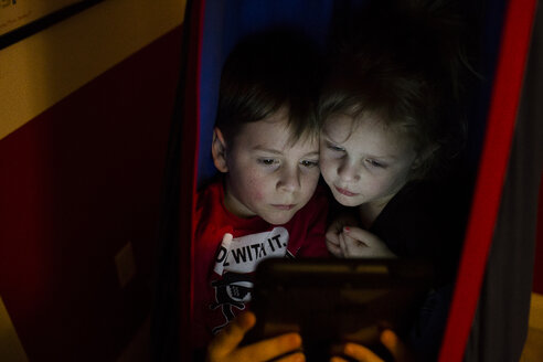 Siblings using tablet computer in tent at home - CAVF43044