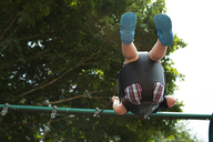Low angle view of boy swinging in park - CAVF43053