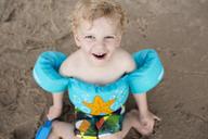Portrait of happy boy wearing water wings sitting at sandy beach - CAVF43077