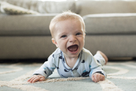 Portrait of cheerful baby boy lying on carpet at home - CAVF43092