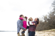 Happy parents embracing daughters at beach against clear sky - CAVF43104