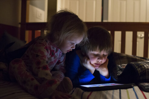 Siblings using tablet computer on bed at home - CAVF43107